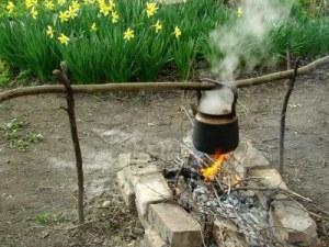 6870341-boiling-water-in-old-sooty-kettle-on-the-hiking-campfire