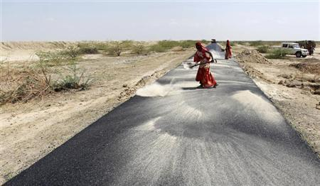 Women labourers throw dust on a road tarmac under construction at Bharadva village in the western Indian state of Gujarat April 23, 2013. REUTERS/Amit Dave