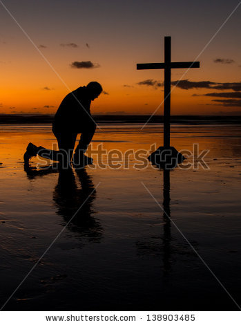 stock-photo-cross-with-a-man-kneel-in-prayer-on-a-beach-at-sunset-138903485