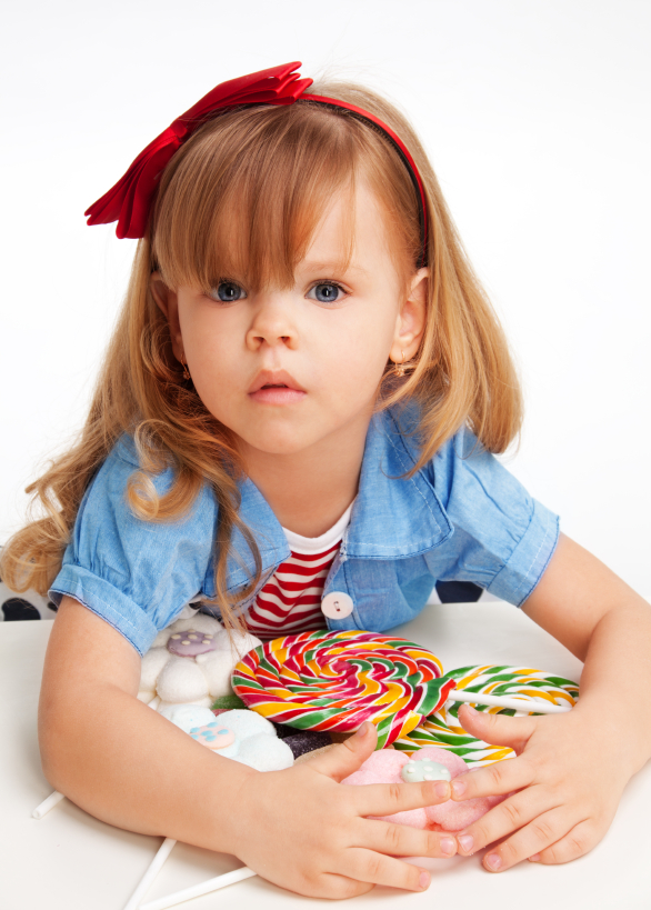 Greedy girl with pile of sweets laying on the table and with troubled expression on the face
