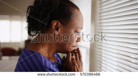 stock-photo-an-older-black-woman-mournfully-looks-out-her-window-570396466